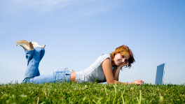 Girl with laptop lying on grass